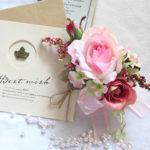 ピンクの流れるようなラインのバラのコサージュ